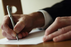Business Writing. A business man or office worker, using a pen to write stock photo