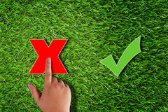Business Wrong Decision Concept. Business wrong decision or answer concept, hand touch redcross on green grass background Royalty Free Stock Photos