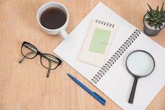 Business's desk of office supplies and gadgets coffee cup, pen, Royalty Free Stock Images