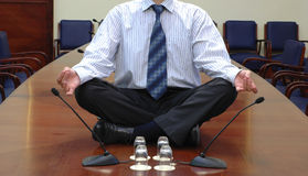 Business yoga. Businessman in yoga pose sitting on the conference table Royalty Free Stock Photo