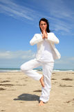 Business yoga. Standing white clothes business woman relaxing concentrated with meditating on the beach with blue sky Royalty Free Stock Photos