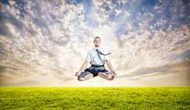 Business yoga levitation. Businessman doing Yoga meditation and levitating under the green grass at sunset sky Royalty Free Stock Images