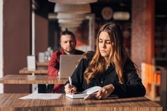 Business young girl writing note in notebook in cafe, man with laptop on background. Business young girl writing note in notebook in cafe, men with laptop on Stock Photography