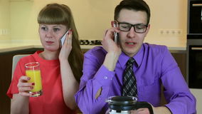 Business young husband and wife talking on smartphone at breakfast. They are busy and do not pay attention to each other. Business young husband and wife talking stock video footage