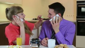 Business young husband and wife talking on smartphone at breakfast. They are in love and caring for each other. stock video