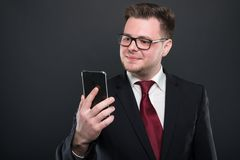Business young man looking at black smartphone. And smiling on black background with copy advertising area royalty free stock photos