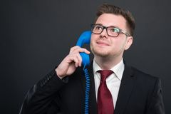 Business young man speaking at blue telephone receiver. On black background with copy advertising area Stock Photos