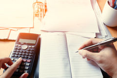 Business young man writing make note report and counting calcula Stock Photo