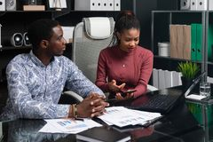 Business young people of African-American nationality working with documents and phone at table in office royalty free stock photo