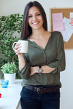 Business young woman drinking coffee in her office. Stock Photography
