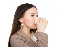 Business young woman drinking from a plastic cup in isolation over white background. Portrait asian woman with long hair in a beige suit royalty free stock photography