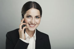 Business young woman on the phone  isolated over a grey backgrou Royalty Free Stock Photos