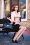 Business young woman sitting on black bench in old city with her handbag before shopping. Waiting for someone. Business young woman sitting on black bench in Royalty Free Stock Photos