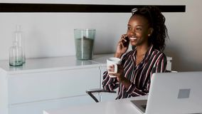 Business young woman talking on mobile phone while drinking coffee in the office. Video of business young woman talking on mobile phone while drinking coffee in stock video footage