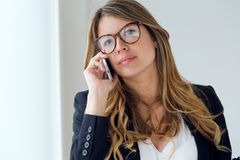Business young woman using her mobile phone in the office. Stock Photo