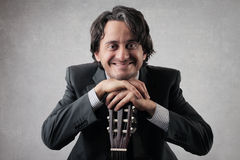 Businessan feliz con una guitarra Imagenes de archivo