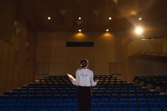 Businessawoman practicing and learning script while standing in the auditorium. Rear view of beautiful Caucasian businesswoman practicing and learning script royalty free stock photography