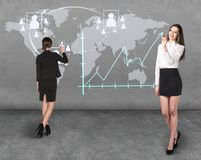 Businessladies in front of the map Royalty Free Stock Images