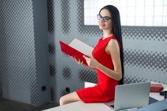 Businesslady attraenti in vestito e vetri rossi si siedono sul tabl Immagine Stock Libera da Diritti