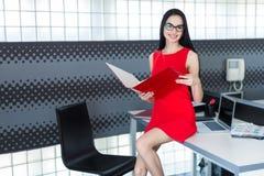 Businesslady attraenti in vestito e vetri rossi si siedono sul tabl Fotografia Stock