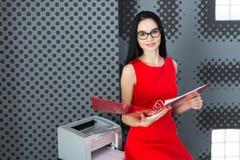 Businesslady attraenti in vestito e vetri rossi stanno vicino al Fotografia Stock