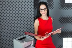 Businesslady attraenti in vestito e vetri rossi stanno vicino al Fotografia Stock Libera da Diritti