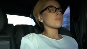 Businesslady cansado en los vidrios que toman una siesta en asiento trasero, trabajar demasiado y la debilidad del coche almacen de video