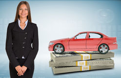 Businesslady with car standing on bundle of money Stock Image