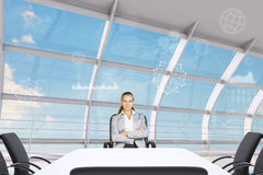 Businesslady with crossed arms sitting at table Royalty Free Stock Photos