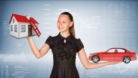 Businesslady holding car and house Stock Photography
