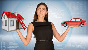 Businesslady holding car and house Royalty Free Stock Photography
