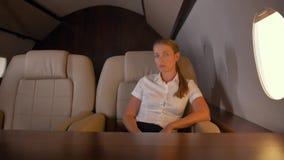 Businesslady near first class private jet porthole stock video