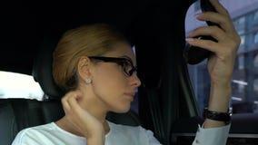 Businesslady que comprueba su maquillaje y peinado, sentándose en asiento trasero del automóvil metrajes
