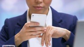 Businesslady que enrolla smartphone usando la aplicación móvil para supervisar activos metrajes
