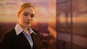 Businesslady que presenta en cámara contra el fondo hermoso de la puesta del sol, anuncio del inicio almacen de video