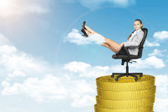 Businesslady sitting in chair on coins stack Royalty Free Stock Images