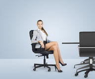 Businesslady sitting half-turned in chair with her Stock Photos