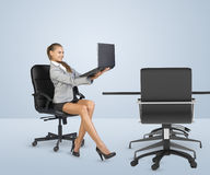 Businesslady sitting half-turned in chair and Royalty Free Stock Image
