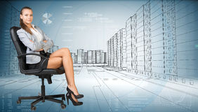 Businesslady sitting half turned with crossed legs Stock Photos