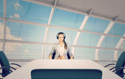 Businesslady sitting at table, using headphones Royalty Free Stock Photography