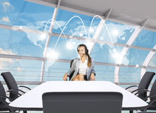 Businesslady sitting at table with world map Stock Photo