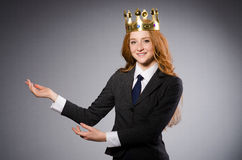 Businesslady wearing crown against gray Royalty Free Stock Image