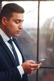 Businesslike man looking into smartphone. Arabian man chatting with business partners.Telephone, modern technology, virtual communication concept Royalty Free Stock Photo