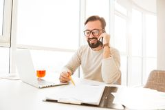 Businesslike man 30s in casual clothing smiling and negotiating. About work using cell phone while working at home Stock Photos
