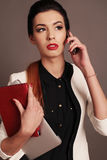 Businesslike woman with dark hair and bright makeup, wears elegant outfit, speaking by mobile. Fashion studio photo of beautiful businesslike woman with dark Stock Photography