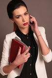 Businesslike woman with dark hair and bright makeup, wears elegant outfit, speaking by mobile. Fashion studio photo of beautiful businesslike woman with dark Royalty Free Stock Photo