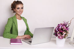 Businesslike woman in elegant outfit working on computer. Fashion studio photo of beautiful businesslike woman in elegant outfit working on computer in office Royalty Free Stock Photo