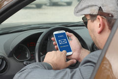 Businessma checking email in a car. Happy male driver smiling while sitting in a car with open front window and checking email on mobile phone. Selective focus Royalty Free Stock Photos