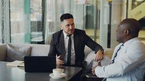2 businessmaen в официально одеждах тряся руки и принимая места на креслах белой кожи для того чтобы обсудить их запуск акции видеоматериалы