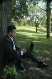 Businessman 1. Businessman in a park with his laptop Stock Images